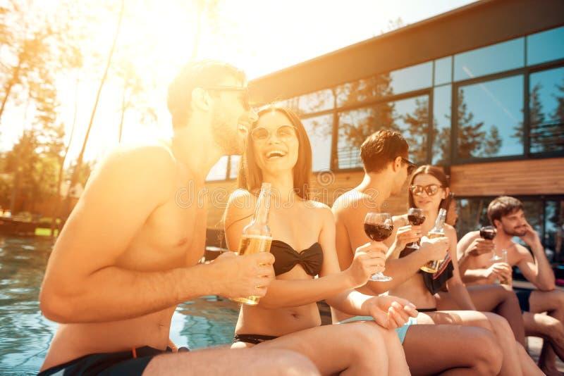 Vänner för sommarsemester på simbassängpartiet Företaget av ungdomarspenderar helg i pöl royaltyfria foton