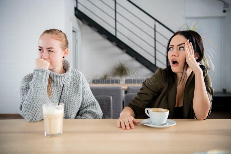 Vänner för unga kvinnor som kränks i kafé, medan dricka kaffe royaltyfria foton