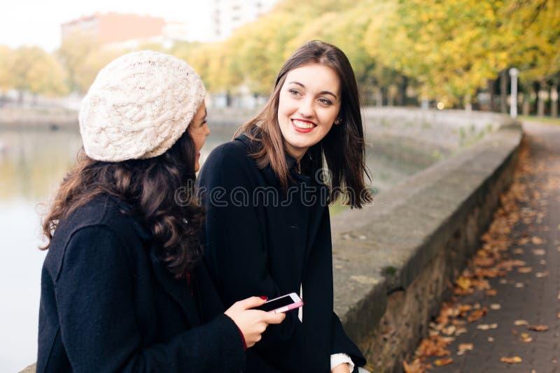 Vänner för unga kvinnor som utomhus talar royaltyfria foton