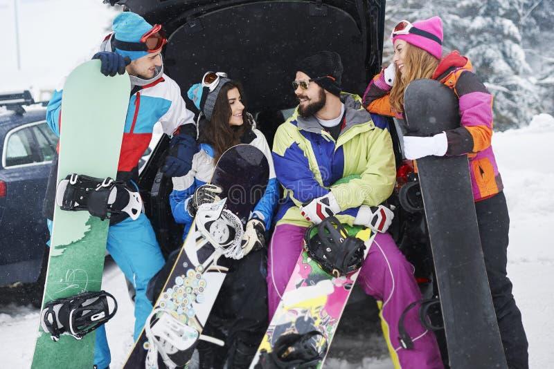 Vänner förbereder sig för snowboarding fotografering för bildbyråer