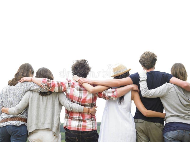 vänner grupperar att krama bakre sikt royaltyfria bilder