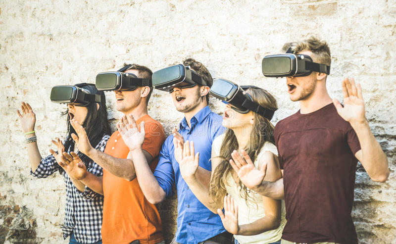 Vänner grupperar att spela på virtuell verklighet för vrexponeringsglas utomhus - arkivbild