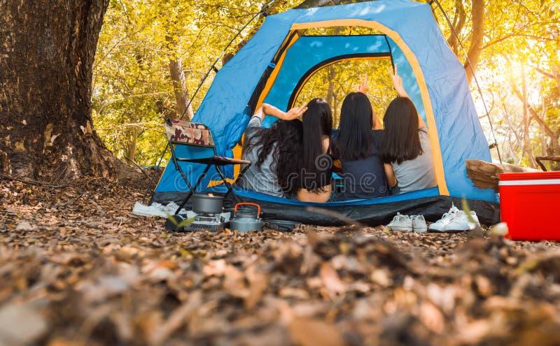 Vänner grupperar av unga asiatiska kvinnor i tältet som tillsammans campar royaltyfri bild