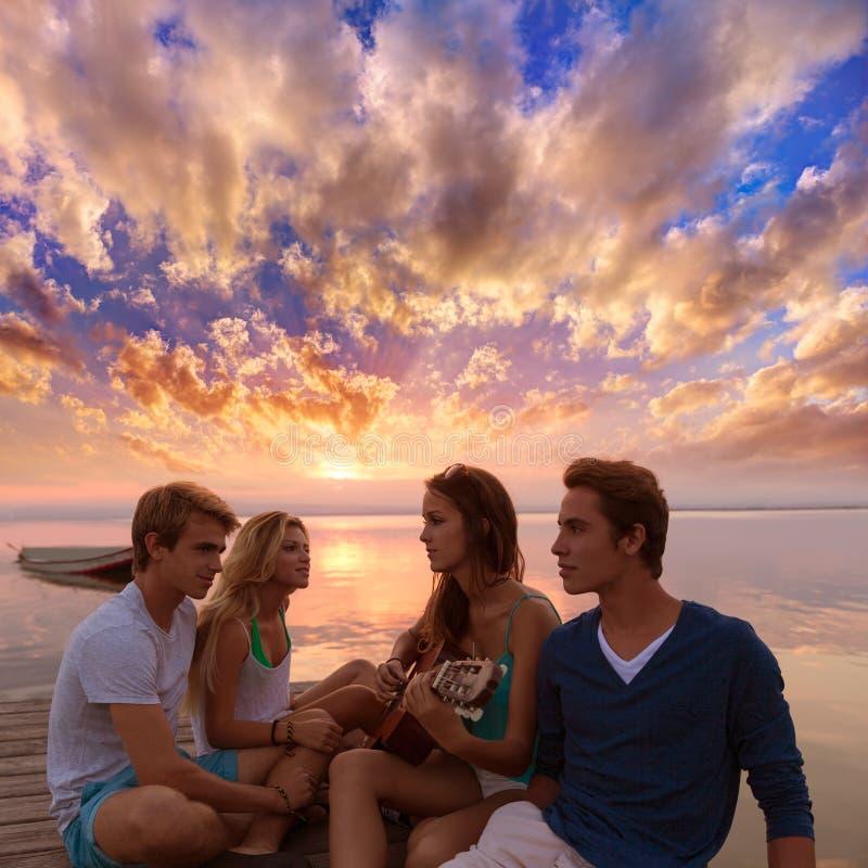Vänner grupperar på solnedgångstranden som har gyckel med gitarren arkivbild