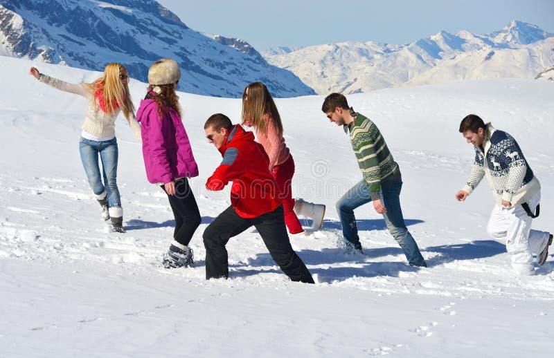 Vänner har gyckel på vintern på ny snö royaltyfri bild