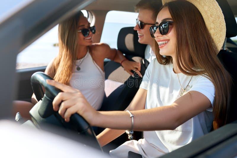 V?nner hyrde en bil f?r sommarv?gtur till stranden Kvinnlig chauff?r i exponeringsglas och sugr?rhatten som har gyckel Kvinnan l? royaltyfria foton