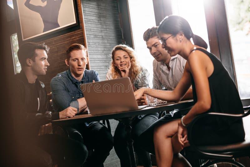 Vänner i coffee shop genom att använda bärbara datorn royaltyfria foton