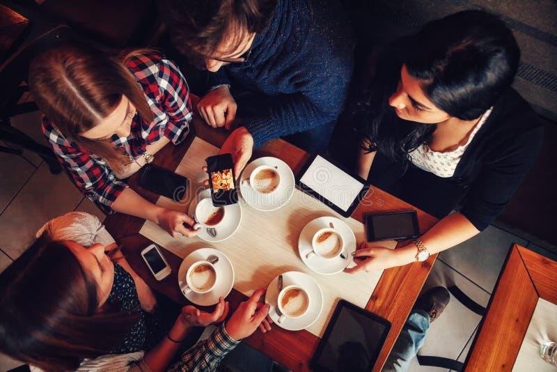 Vänner i kafé som dricker kaffe arkivbild