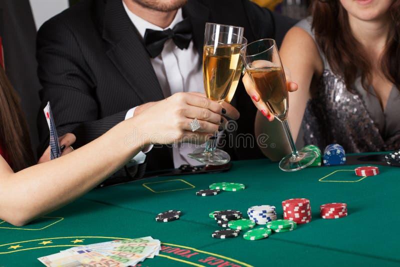 Vänner i kasinot som lyfter exponeringsglas royaltyfria bilder