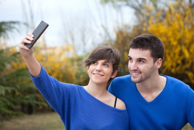 Vänner i parkera som tar fotoet med mobiltelefonen fotografering för bildbyråer