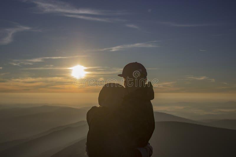 Vänner i solnedgång i berg royaltyfria bilder