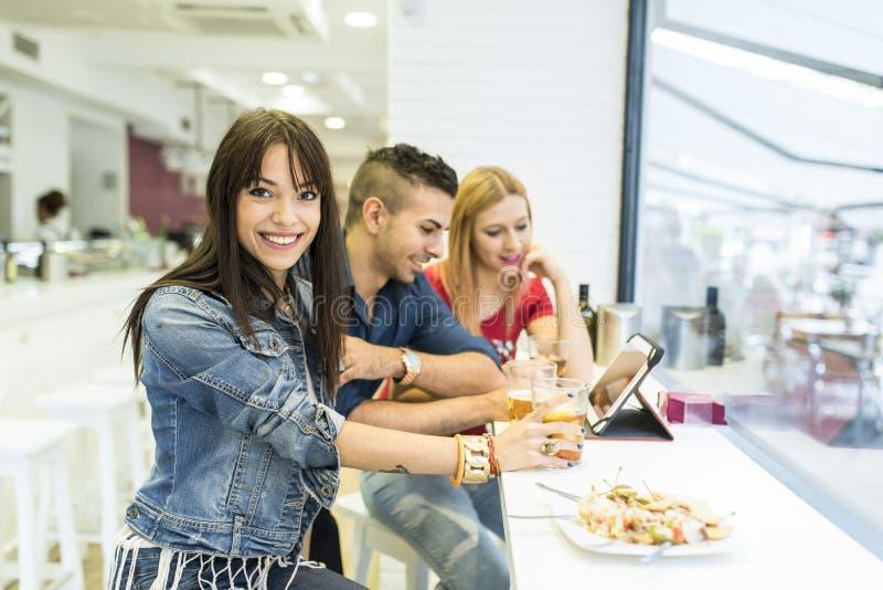 Vänner i stång, tre ungdomarsom dricker i restaurang arkivfoton