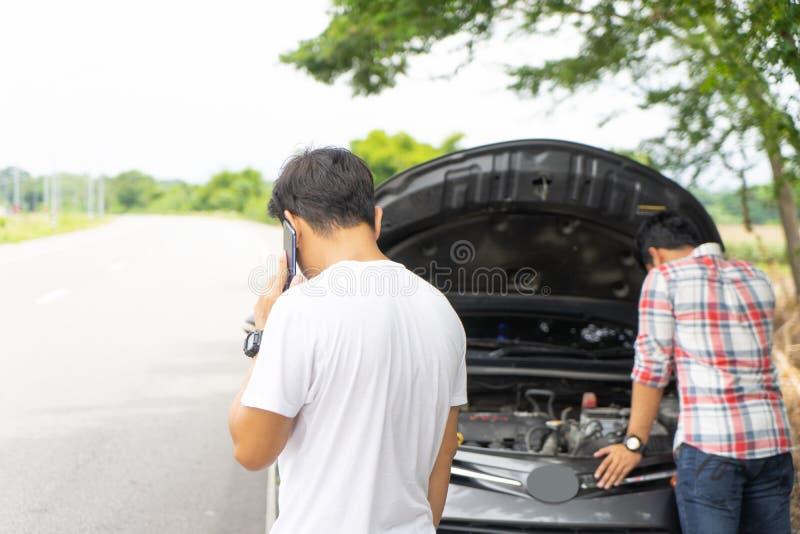 Vänner kallar och fixandebilen bruten down vid vägrenen Par royaltyfria bilder