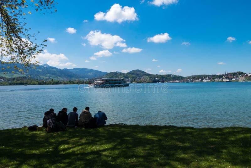 Vänner kopplar av och spenderar ferie vid sjön royaltyfri fotografi