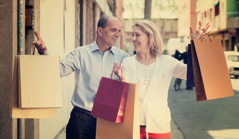 Vänner kopplar ihop att ha shopping turnerar, i stad och att le royaltyfri foto