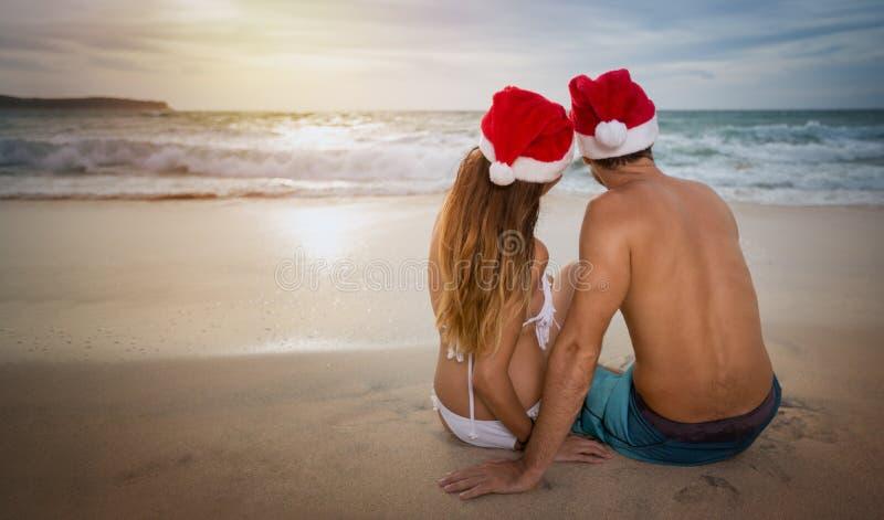 Vänner kopplar ihop i santa hattar på den tropiska sandiga stranden royaltyfria foton