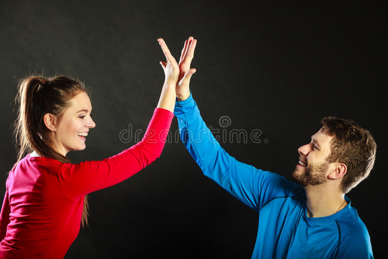 Vänner man och kvinnan som firar ge höjdpunkt fem royaltyfria bilder