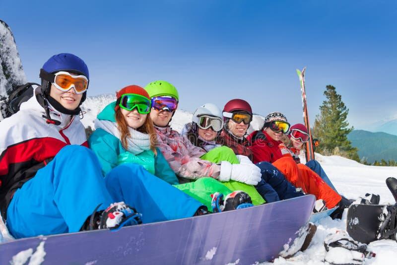 Vänner med att bära för snowboards skidar googlar arkivbild