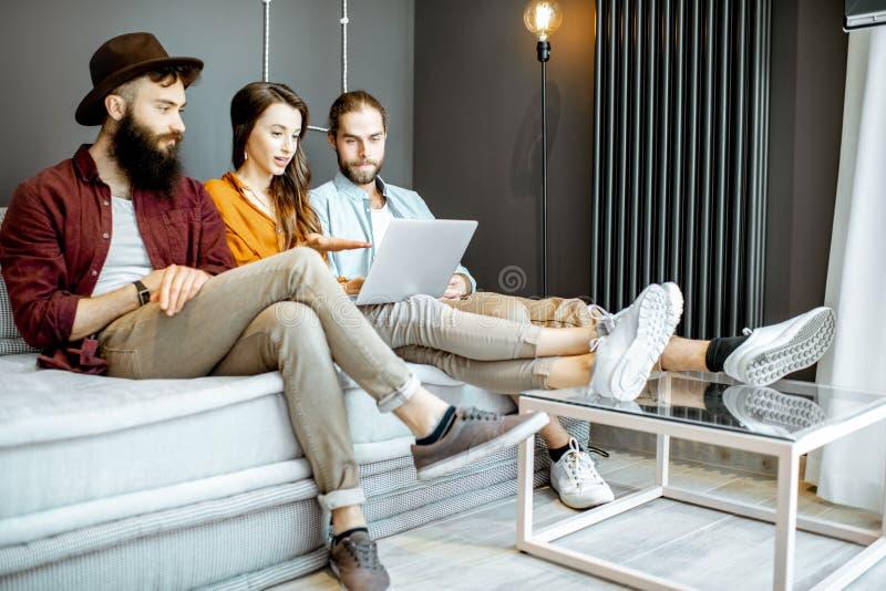 Vänner med bärbara datorn hemma royaltyfri bild