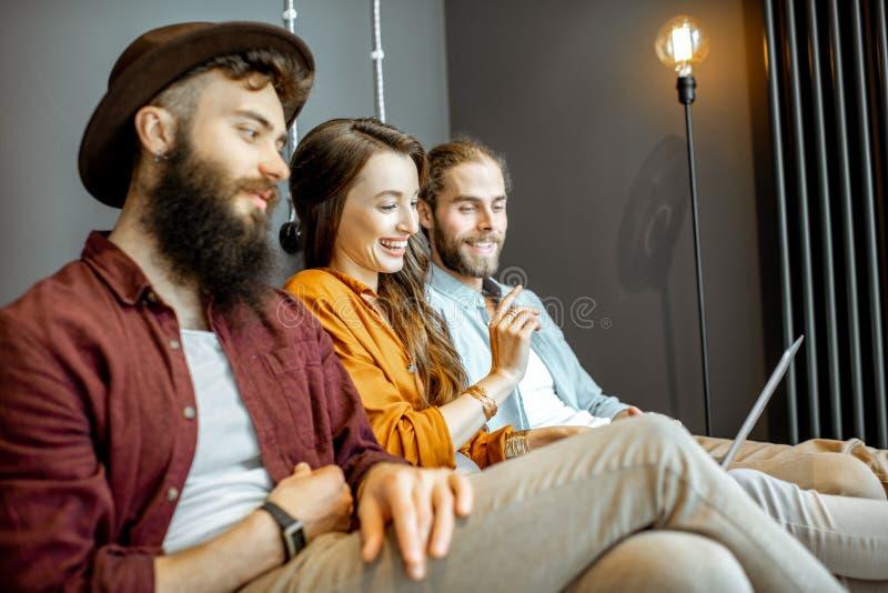 Vänner med bärbara datorn hemma arkivbild