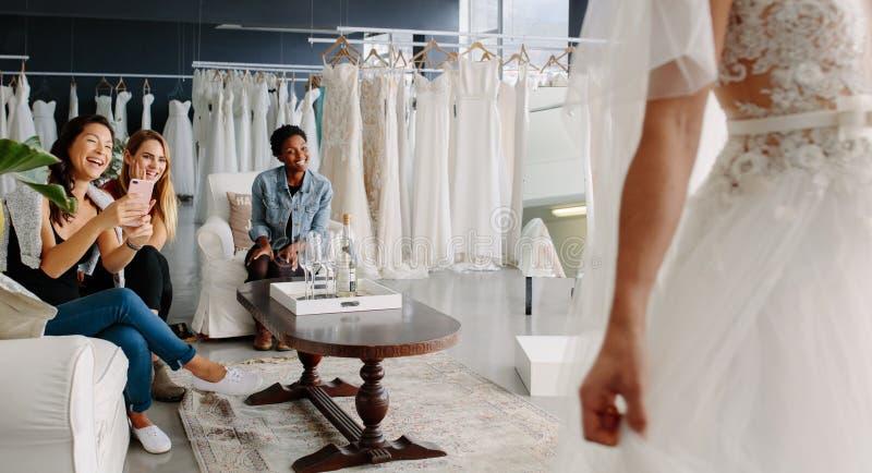 Vänner med bruden i brud- klänningprovhytt arkivfoton