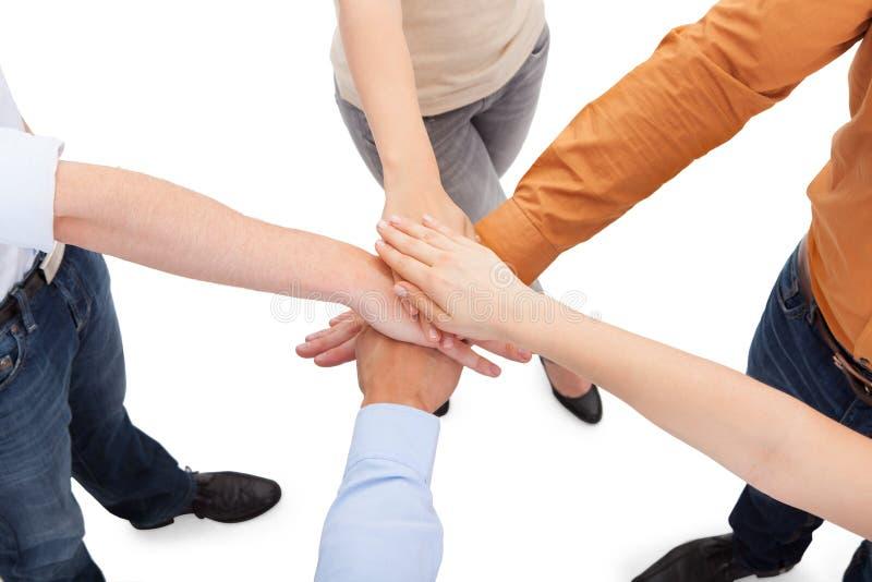 Vänner med deras händer som tillsammans staplas arkivbild