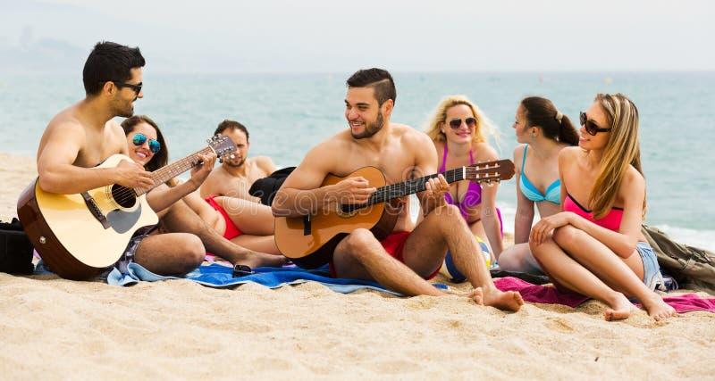 Vänner med gitarren på stranden royaltyfria bilder