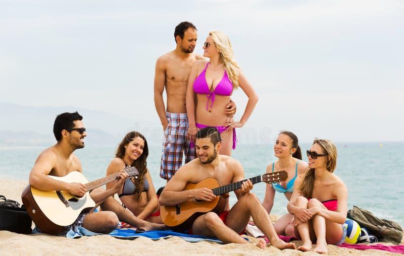 Vänner med gitarren på stranden royaltyfri fotografi
