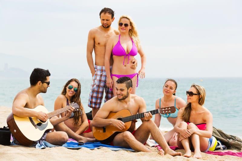 Vänner med gitarren på stranden royaltyfria foton