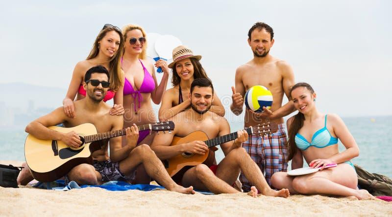 Vänner med gitarren på stranden royaltyfri foto