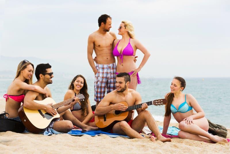 Vänner med gitarren på stranden royaltyfri bild