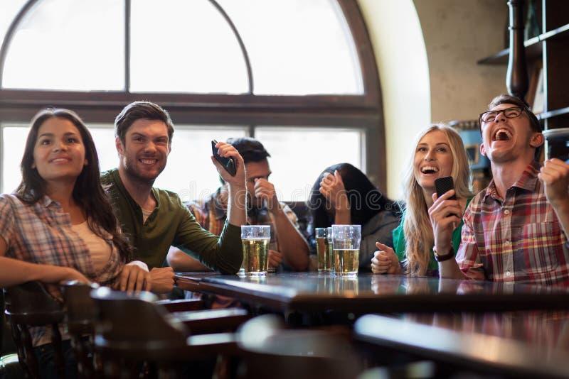 Vänner med hållande ögonen på fotboll för öl på stången eller baren royaltyfri fotografi