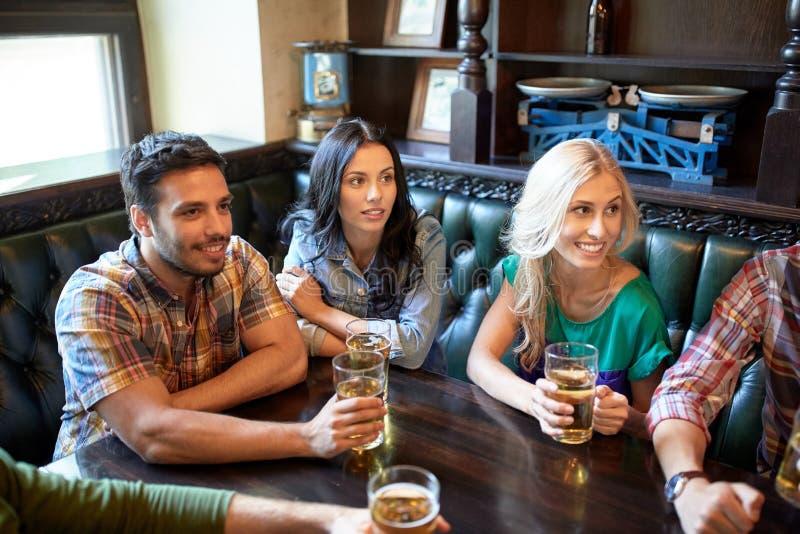 Vänner med hållande ögonen på fotboll för öl på stången eller baren royaltyfri foto