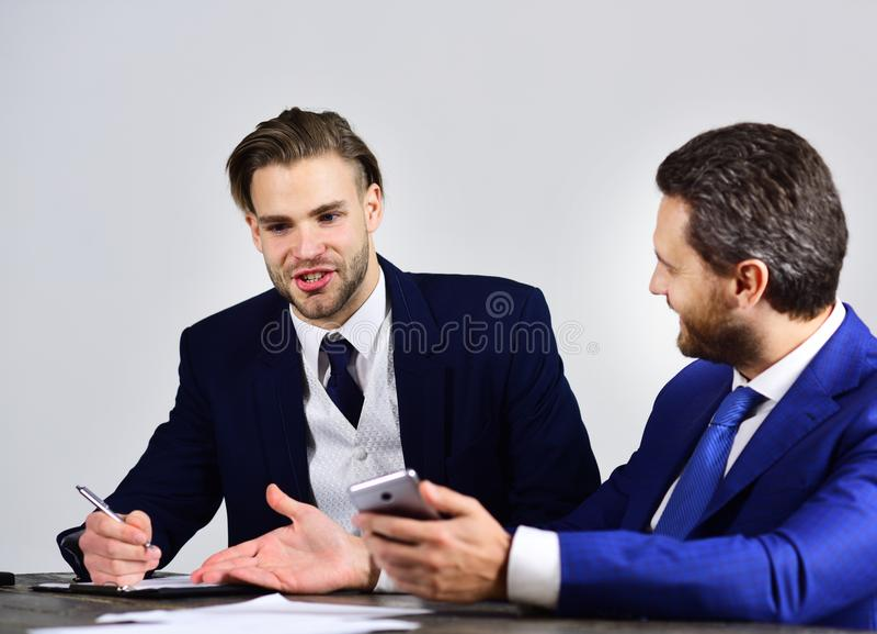 Vänner med lyckliga framsidor diskuterar start- och bränninginternet royaltyfri bild