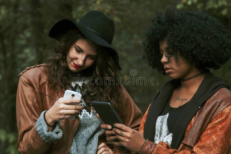 Vänner med mobiltelefonen royaltyfria foton