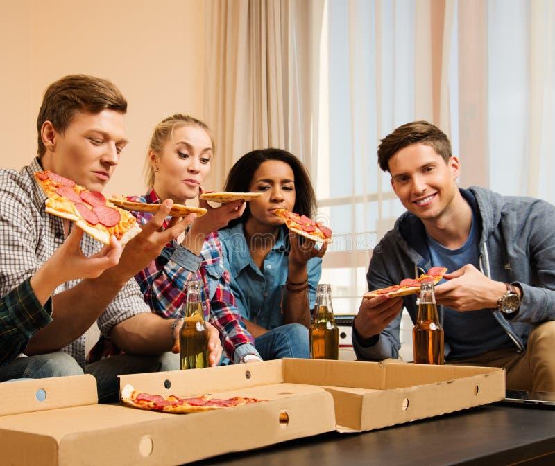 Vänner med pizza och flaskor av drinkar som har partiet arkivfoton
