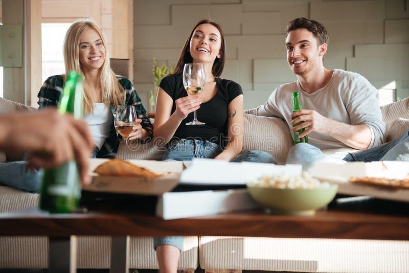 Vänner med pizza, vin och öl som talar på soffan royaltyfri foto