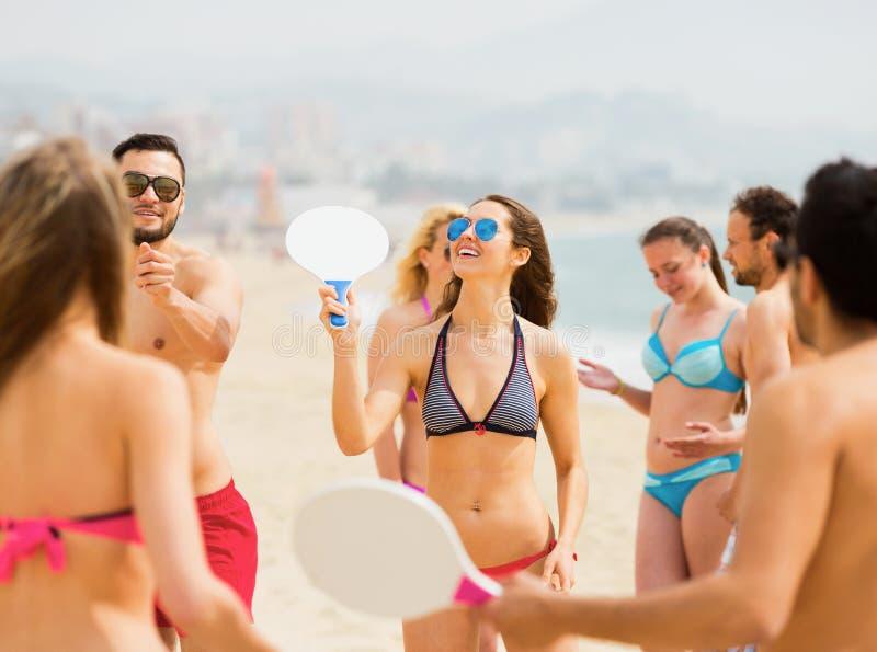 Vänner med racket som kopplar av på den sandiga stranden royaltyfria foton