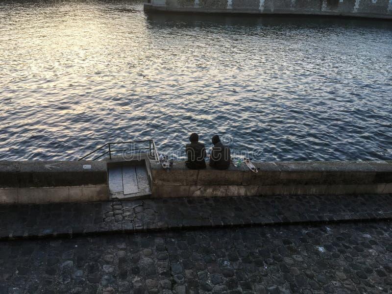 Vänner med skateboarder sitter vid Seinen på en vinterafton i Paris arkivfoton