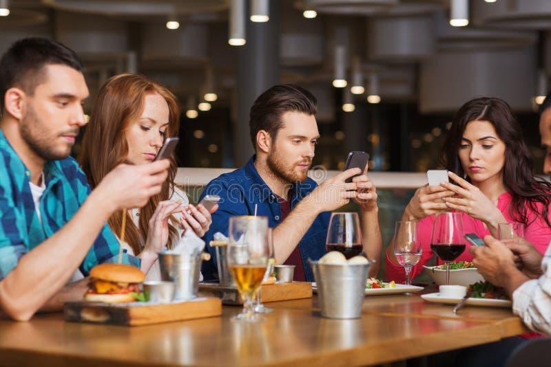 Vänner med smartphones som äter middag på restaurangen royaltyfria foton