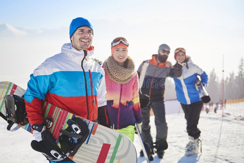 Vänner med snowboards och skidar arkivbild