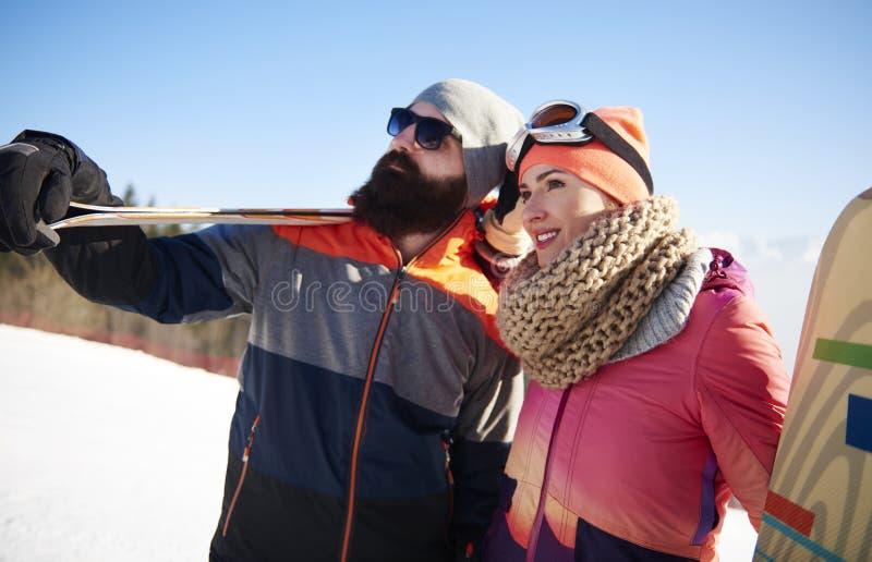 Vänner med snowboards och skidar royaltyfri fotografi