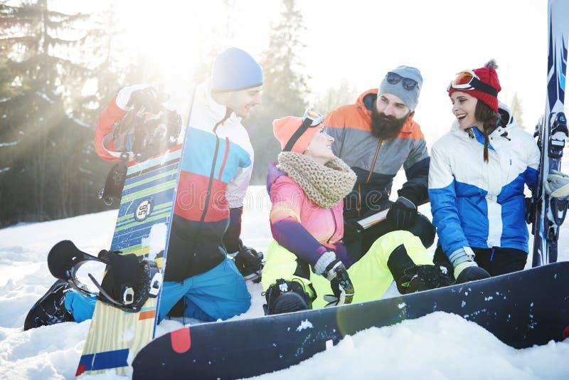 Vänner med snowboards och skidar arkivfoton