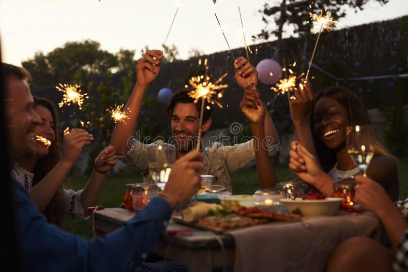 Vänner med tomtebloss som äter mat och tycker om partiet royaltyfria foton