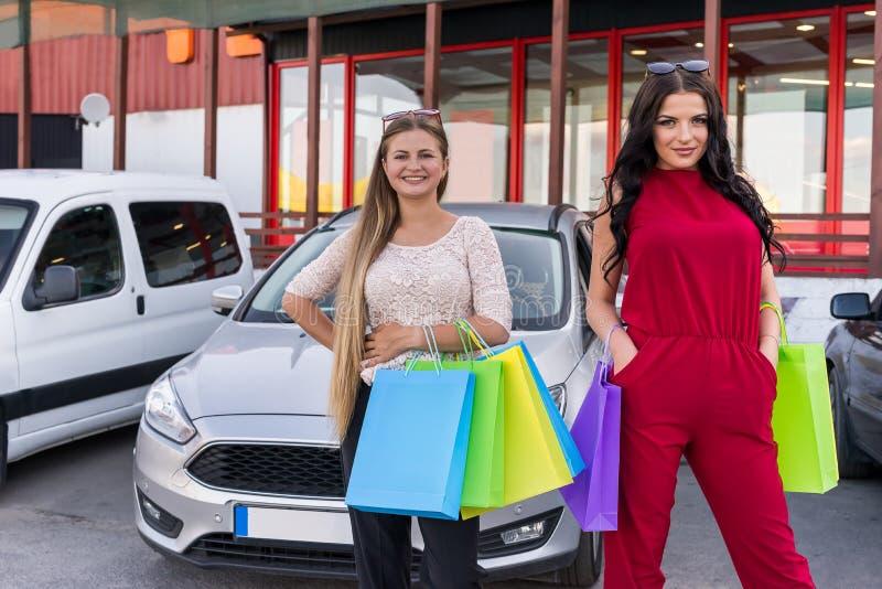 Vänner, når att ha shoppat med färgglade påsar på parkering royaltyfri foto