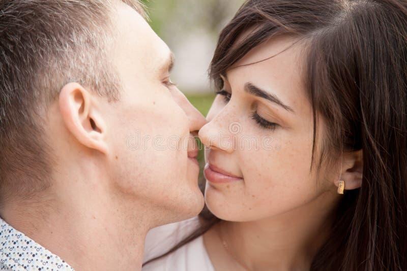 Vänner omkring som ska kyssas royaltyfri fotografi