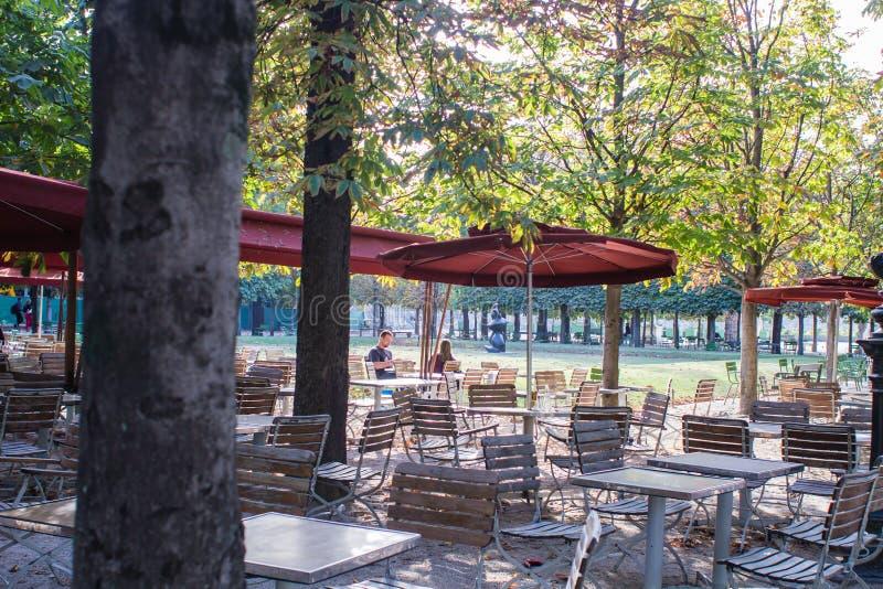 Vänner sitter på en kafétabell i Tuileriesen, Paris, Frankrike fotografering för bildbyråer