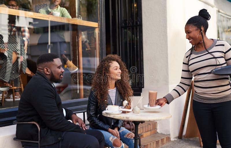 Vänner som är betjänad av deras servitris på ett trottoarkafé arkivfoto