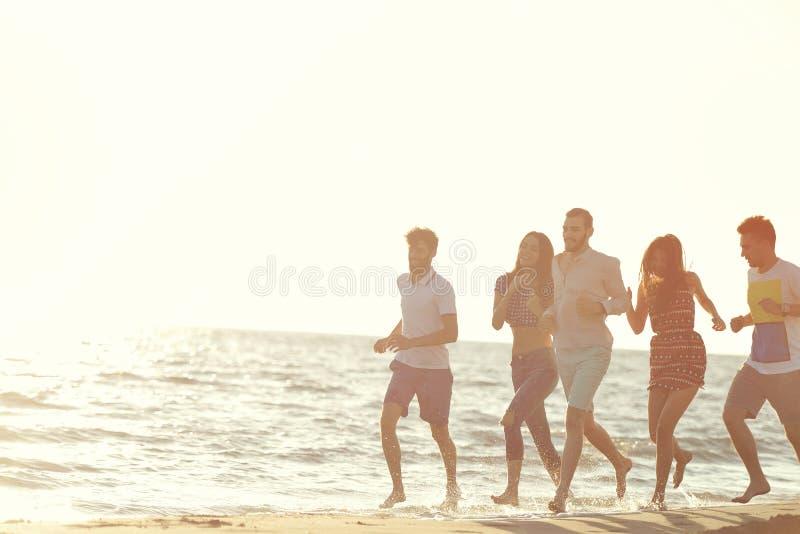 Vänner som är roliga på stranden under solnedgångsolljus arkivbild