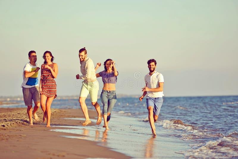 Vänner som är roliga på stranden under solnedgångsolljus royaltyfria bilder